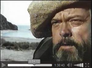 Fotograma de la pelicula en la que Orson Welles al fondo la playa de El Sombrerico